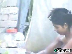 Mal Mujer lavándose las del cuerpo al aire libre
