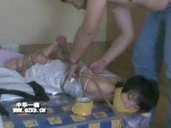 Chinese girl struggling under tight rope bondage