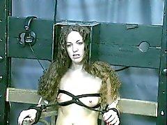 Suloinen ruskeahiuksin on sidottu , katsoo Teat kidutusta vankihuoneessa