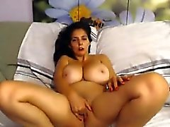 Brunette with huge natural tits masturbates on the sofa