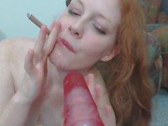 Chubby Redhead Smoking On A Dildo