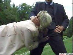 Yaşlı bayan genç adam çimlerin etrafında oynamak
