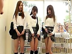 Kolmella adorable Aasian koulutyttöjen työtä niiden ihana huulilla koskevasta