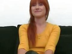 Redhead girl teasing on black couch