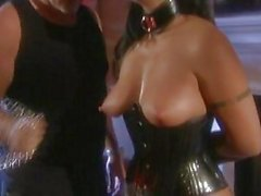Hot brunette in leather corset and fishnet stockigns gets tied and tortured