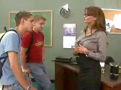 Busty brunette leraar neukt en zuigt haar twee studenten in trio