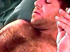 Mature poilue type Sam solo joue devant une bite bien sucer
