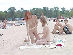 Freche junge Nudisten miteinander spielen in Sand