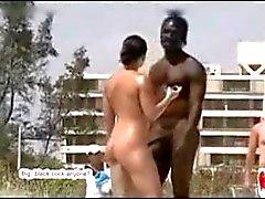 Zeer sexy hing zwarte kerel op naakt strand met wit meisje