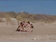 Couple split by strangers on a beach