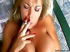 Busty blond Amber röker samtidigt som de får hennes fitta slickad och sedan blir spikade