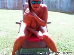 Tanned MILF with mature look tits oiling up in her back yard