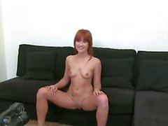 Redhead princess teasing on black sofa