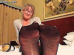 Beautiful grey haired grandma gives a footjob