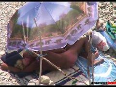 Handjob on candid beach with old nudist couple