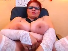 Shot-haired MILF redhead plays with her own boobs and beave