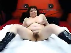 Busty mature lady in black boots reveals her hairy cunt on
