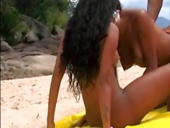 Ebony and Asian girls on the beach tear into a hard cock together