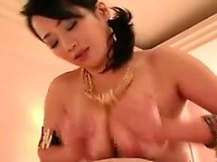 Bodacious Asian lady massages a thick cock with her huge na