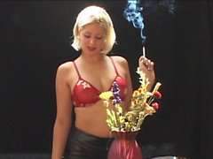 Sexy blonde is posing in her bra by potted flowers having a