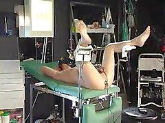 Mistress pukeutunut lateksista on hänen orja sidottuna ja elektro iskuja hänen pähkinät