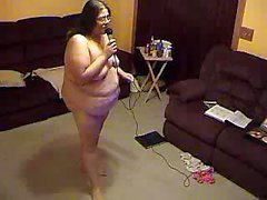 Fat Alma Smego is standing in her bedroom and singing naked