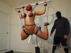 Cum Whore is suspended by her tits, machine fucked, cropped and flogged