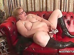 Mature in glasses masturbates on leather sofa