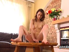 Breathtaking cutie is pissing and pleasing shaved pussy