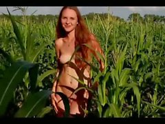 Young skinny teen outside in the corn field showing her young body
