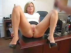 Mature blonde secretary spreads her legs and masturbates on the desk
