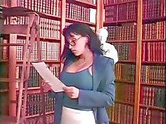 Jonge blonde schoolmeisje en rondborstige brunette bibliothecaris spelen met een strapon in de bibliotheek