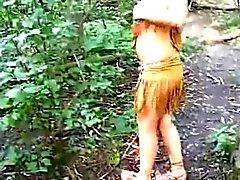 Chica vestida como indio aspira el martillo en los bosques